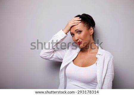 Beautiful girl is looking at the camera with shame. She is touching her forehead with embarrassment. Isolated on grey background and there is copy space in left side - stock photo