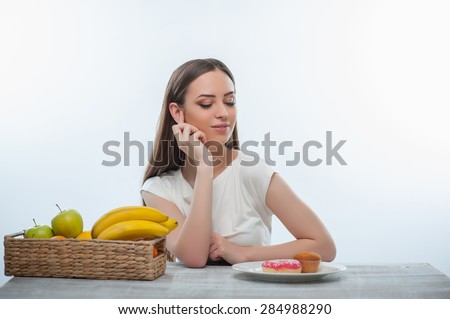 Beautiful girl is looking at unhealthy donuts and can not resist the temptation. She is sitting at the table. Isolated on a white background - stock photo