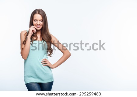 Beautiful girl is looking down with shyness. She is smiling and touching her face with her hand. Isolated on background and copy space in left side - stock photo
