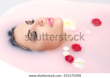 Beautiful girl is lying in bath and relaxing. She closed her eyes with enjoyment - stock photo