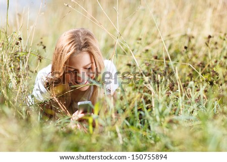 Beautiful girl is lying in the grass and writing sms on the phone in the city park at summer. - stock photo