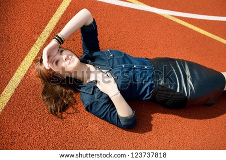 Beautiful girl is lying on playground and looking up. - stock photo