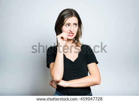 beautiful girl is nervous and bites nails, studio photo isolated on a gray background - stock photo