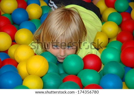 Beautiful girl is playing in box of balls at playground - stock photo
