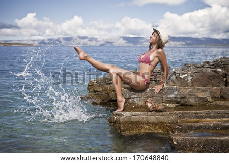Beautiful girl is playing with water on the beach - stock photo