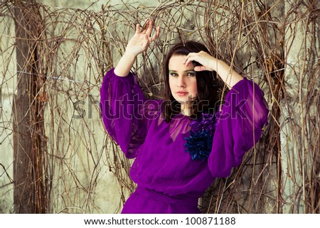 Beautiful girl is posing. Focus on face. Old building and bushes on a background. - stock photo