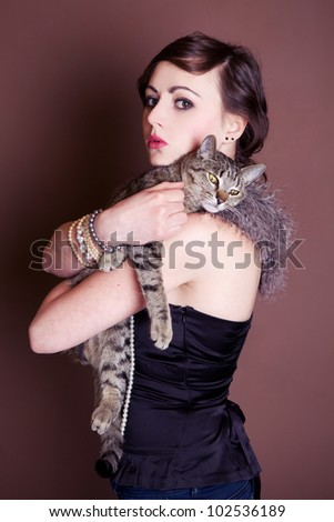 Beautiful girl is posing with cat. Focus on face.