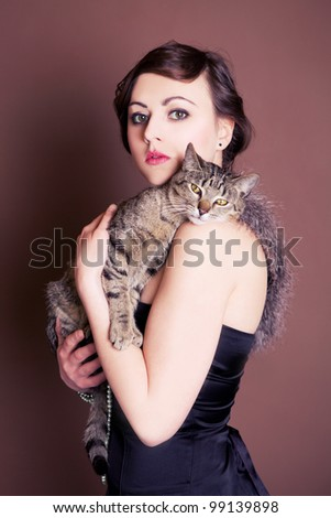 Beautiful girl is posing with her cat. Vintage shoot. - stock photo