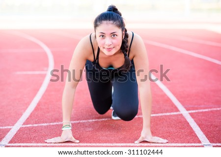 Beautiful girl is ready to run on the running track - stock photo