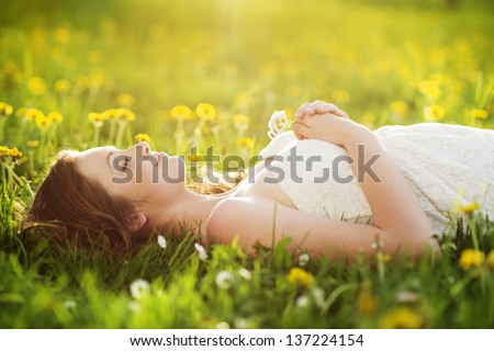 Beautiful girl is relaxing lying on the grass in the garden - stock photo