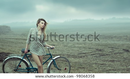 beautiful girl is resting next to the bike - stock photo