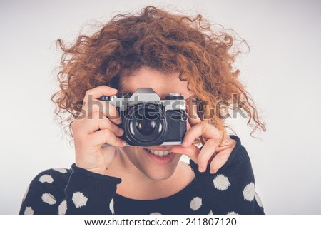 beautiful girl is shooting with a retro camera. isolated on whit - stock photo