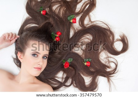 Beautiful girl is showing her perfect long hair with red roses on it. She is lying and smiling. The lady is looking at camera happily - stock photo