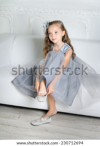 Beautiful girl is sits on the sofa and puts on her shoe