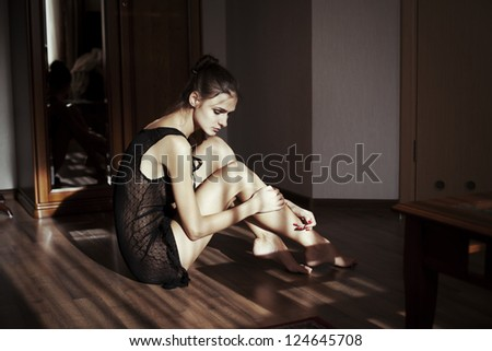 Beautiful girl is sitting in her underwear in the hotel room - stock photo