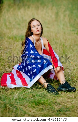 Beautiful girl is sitting on the grass with the American flag