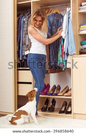 Beautiful girl is smiling and looking at her dog while choosing clothes in a dressing room - stock photo