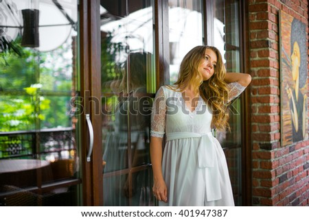 Beautiful girl is standing next to the big window