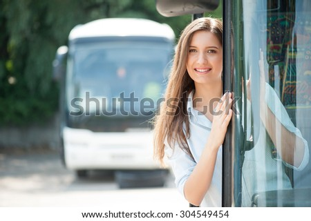 Beautiful girl is standing on doorsteps of the bus. She is looking at the camera and smiling. The lady is enjoying her trip. Copy space in left side - stock photo