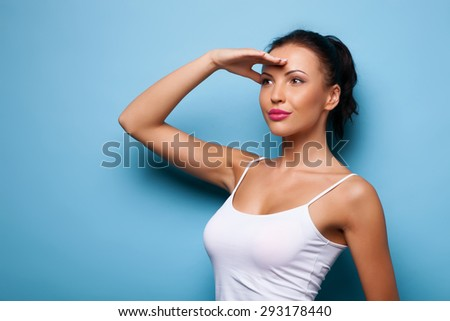 Beautiful girl is touching her hand to her forehead. She wants to watch interesting view. She is looking forward with curiosity.  Isolated on blue background - stock photo