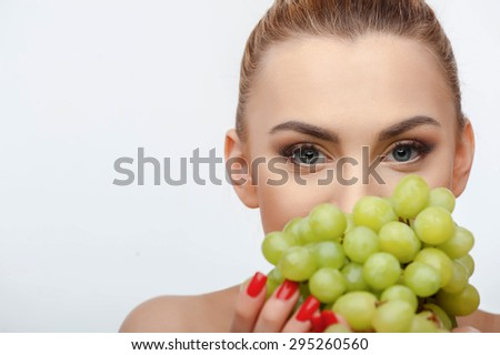 Beautiful girl is touching to her mouth bunch of grapes. She is looking at the camera with desire. Isolated on background and there is copy space in left side - stock photo
