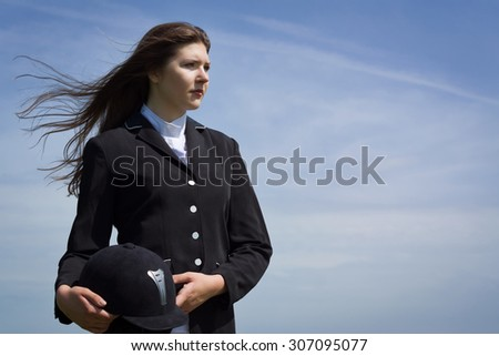 Beautiful girl jockey dressing uniform posing outdoors