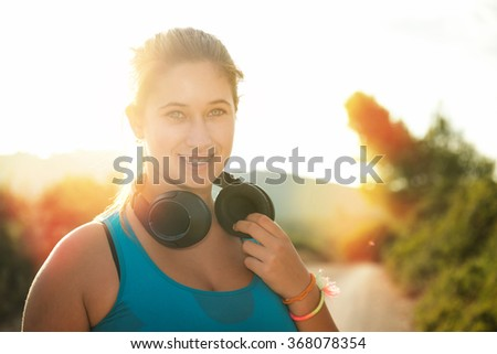 Beautiful girl jogger outdoors with headphones - stock photo
