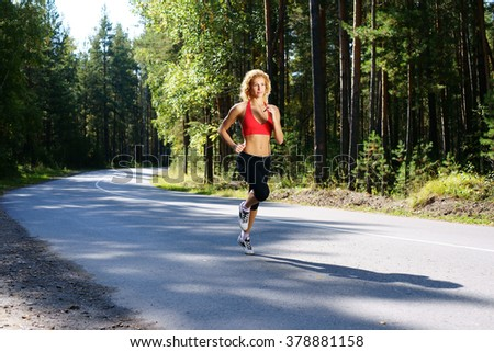 beautiful girl jogging in the forest - stock photo