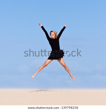Beautiful girl jumping on the sand  dune. - stock photo