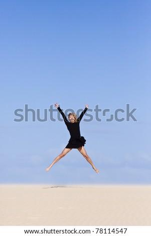 Beautiful girl jumping on the sand  dune. - stock photo