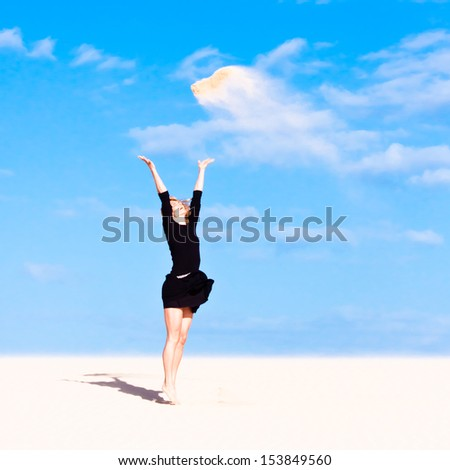 Beautiful girl jumping on the sand dune. Clear blue sky in the background. - stock photo