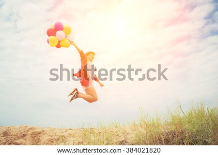 Beautiful Girl jumping with balloons on the beach - stock photo