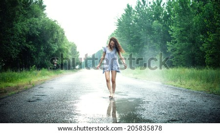 Beautiful girl jumps in a puddle on the road - stock photo