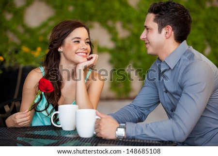 Beautiful girl just got a red rose from her boyfriend on a date at a cafe