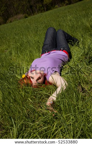 Beautiful girl laing in a green grass