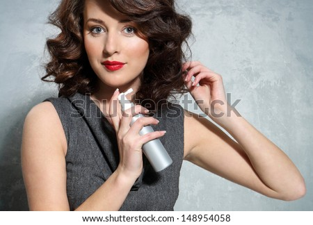 Beautiful girl laying fixes using hairspray - stock photo