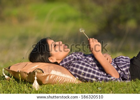 Beautiful  girl laying on pillow and blowing white dandelion in the forest