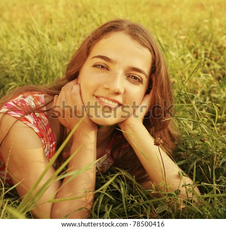 beautiful girl lays on a grass - stock photo