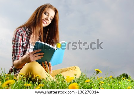 Beautiful girl lies on meadow and reads the boo - stock photo