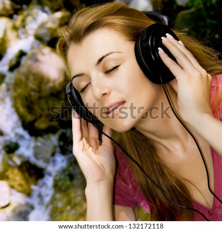 Beautiful girl listen music by headphones in natural environment. - stock photo