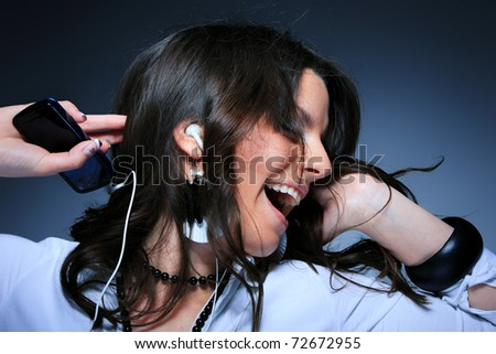 Beautiful Girl listening music with her cell phone over blue background - stock photo