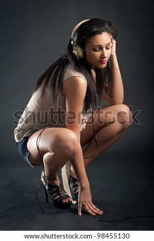 Beautiful girl listening to music against dark background.