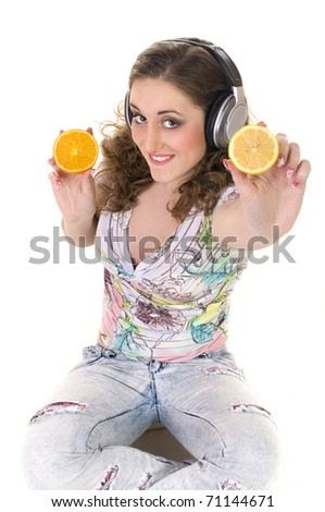 beautiful girl listens music and eats orange