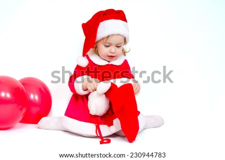 Beautiful girl looking for Christmas gifts in the Christmas sock on white background