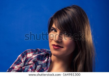 Beautiful girl looking in camera. Fashion woman portrait on dark blue background. Beautiful girl looking in camera. Fashion close-up woman portrait on dark blue background. Country style picture. - stock photo