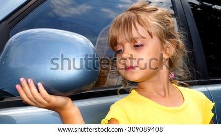 Beautiful girl looking in car back rear-view mirror  - stock photo