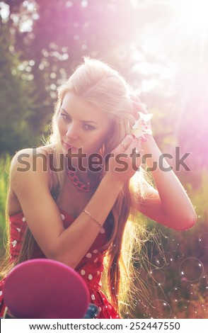 Beautiful girl looks in a mirror on a background of nature - stock photo