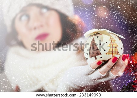 beautiful girl looks with dreamy eyes a Christmas decoration - stock photo