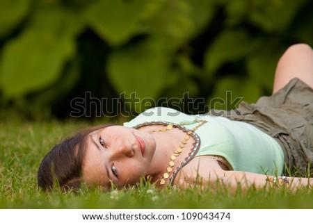 Beautiful girl lying down at grass - stock photo