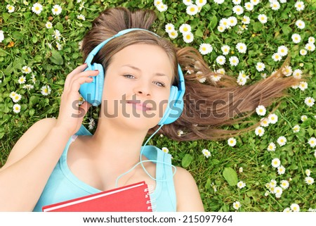 Beautiful girl lying in a meadow and listening to music on headphones - stock photo